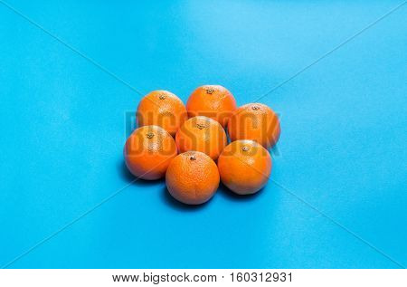 Sun symbol from Six Colorful fresh orange mandarins laid out on blue table viewed from above with copy space.