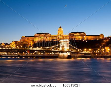 Illuminated Buda Castle and Chain Bridge over Danube River in Budapest by night, Hungary, Europe. UNESCO World Heritage Site. Long exposure shot with blurred water stream.