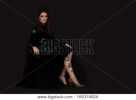Bug queen woman with crown wearing black dress with dress with luminous beetles