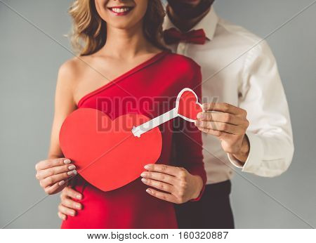Cropped image of beautiful elegant girl in red dress and guy in classic shirt and red bow tie holding a paper heart and smiling on gray background