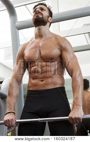 Strong fit man lifting weights in the gym