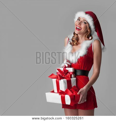 Happy girl in Santa style dress and hat with stack of Christmas gifts