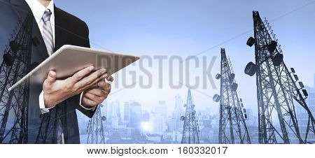 Businessman working digital tablet, with double exposure panoramic cityscape and telecommunication towers in sunrise