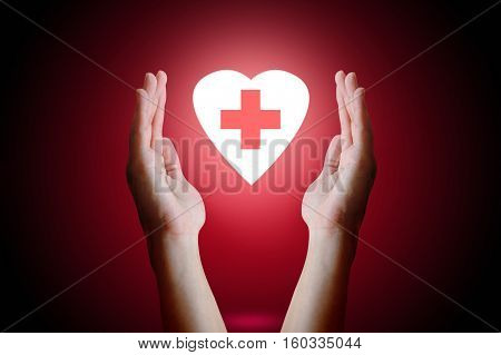 Healthcare concept Woman hand holding and protect heart with medical symbol inside on red background.