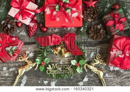 Christmas festive setting decorations with bells wreath gift boxes fir tree cones red ornament and gold reindeer with snowflake on wooden table