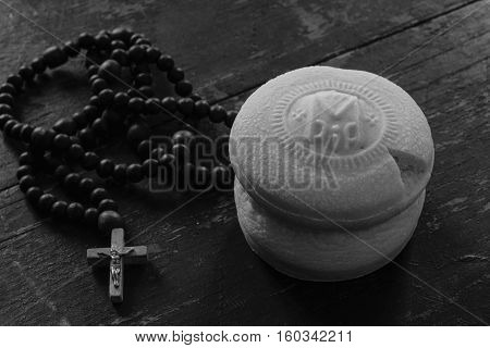 Theotokion service unleavened bread taken out with a particle for Eucharist in the Orthodox Church and the rosary with a crucifix close-up. black and white photo