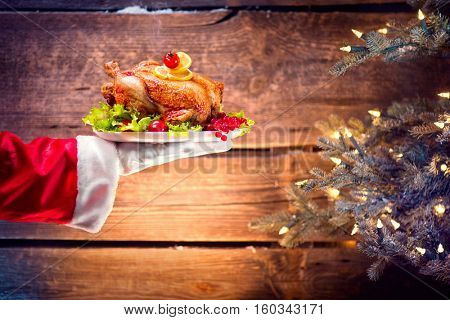 Christmas Holiday dinner. Santa Claus hand holding roasted Chicken. Christmas and New Year food concept, over rural wooden background and Decorated Christmas tree with lights.