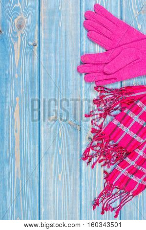 Woolen gloves and shawl for woman on old boards warm clothing for autumn or winter womanly accessories copy space for text