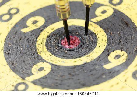 Macro of dart arrows in an old dartboard.