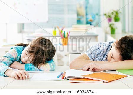 Tired schoolchildren fell asleep on desk in classroom