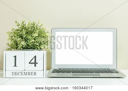 White wooden calendar with black 14 december word with white blank space at center of computer notebook on white wood desk and cream wallpaper textured background selective focus at the calendar