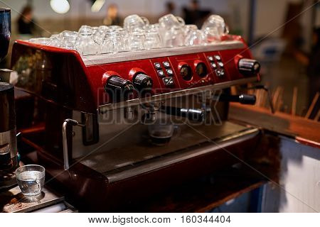 Female bartender in the workplace. Girl makes coffee using coffee machine. Coffee cappuccino coffee coffee shop the bartender - the concept of catering. Use in articles about coffee.
