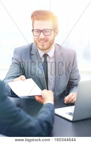 Businessman giving paper to hos colleague in office