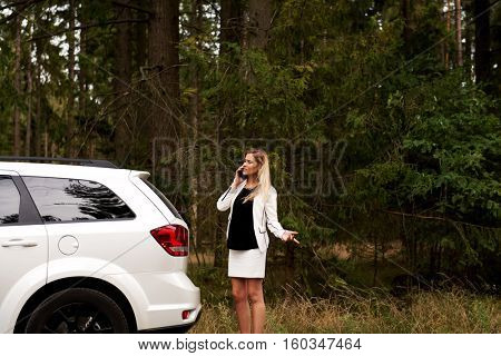 Young woman with broken car calling for help