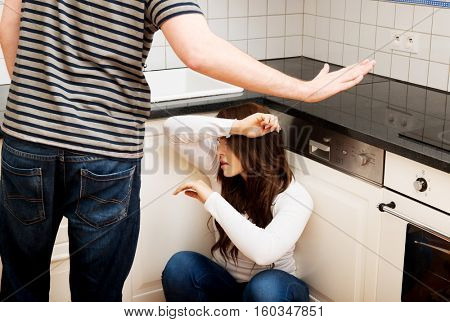 Men shouting on his girlfriend in the kitchen.