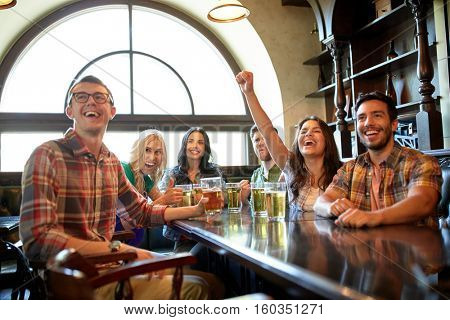 people, leisure, friendship and entertainment concept - happy friends drinking beer, watching sport game or football match and celebrating victory at bar or pub