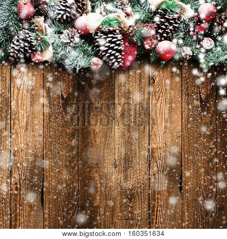 Merry Christmas Frame with Snow and real wood green pine, colorful baubles, knots with berries and other seasonal stuff over an old wooden aged background