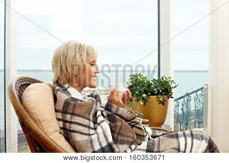 Senior woman sitting in armchair and drinking hot tea