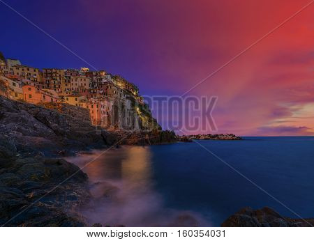 Cinque Terre colorful traditional houses on a rock over Mediterranean sea after sunset at the dusk, Manarola, , Italy, Ligurian Coast.