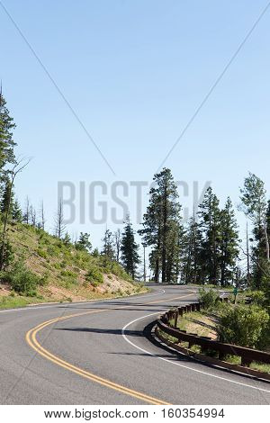looking up an s curve of a winding sloped road framed by hills and trees.