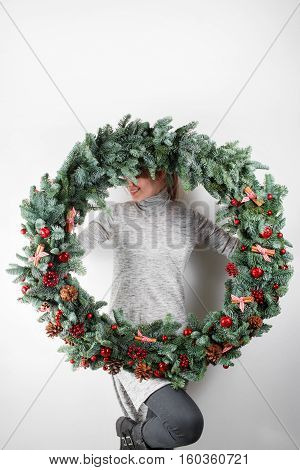 young woman holding christmas large wreath in hands in light, seasonal holidays, rustic theme, adorning.