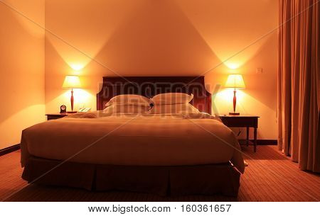 King size bed in a hotel room in the night
