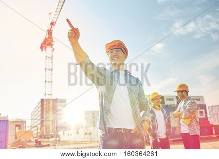 business, building, teamwork and people concept - group of smiling builders in hardhats pointing finger aside on construction site