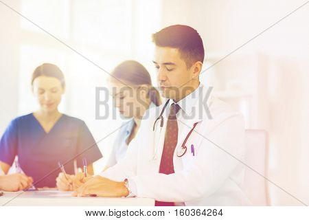 hospital, profession, people and medicine concept - group of happy doctors meeting and taking notes at medical office