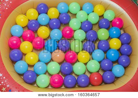 Many colour plastic balls toy hovering above the water .