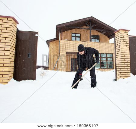 Man cleans snow shovel around the house