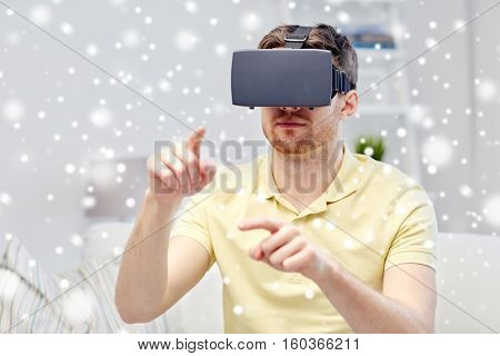 technology, augmented reality, winter, christmas and people concept - young man with virtual headset or 3d glasses playing video game over snow