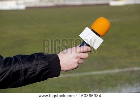 hand hold microphone for interview, after football game