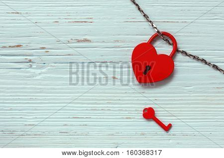 Heart shaped padlock with key on wooden background