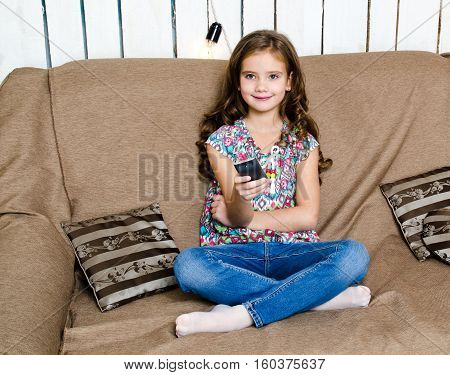 Cute little girl holding a remote control and sitting on the sofa
