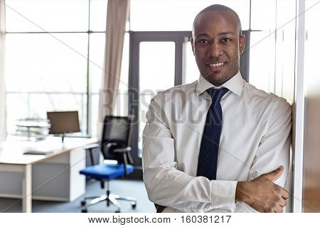 Portrait of smiling young businessman with arms crossed leaning on cupboard in office