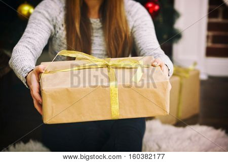 Young woman keeps a paper gift in hands