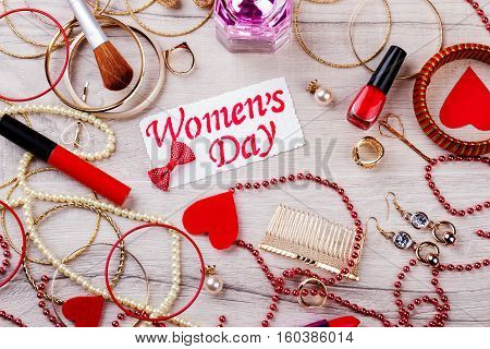 Women's Day card with jewelry. Make-up products near hearts. Stylish and expensive look. Getting ready for holiday.