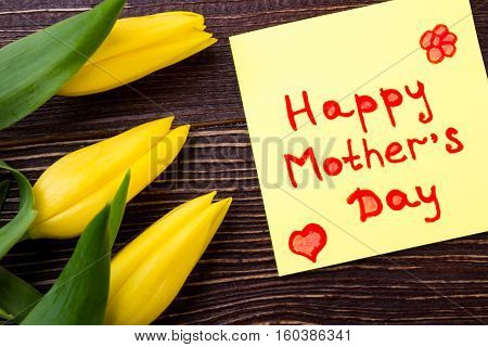 Mother's Day card and tulips. Greeting paper and flowers. Create bright present for mom. Expectation of holiday.