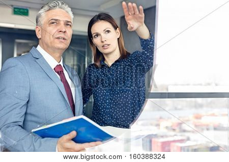 Young businesswoman showing something to mature businessman seen through glass