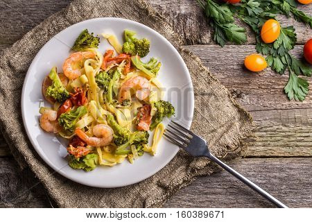 Pasta linguine with shrimps and broccoli in plate on wooden background. Flat lay.