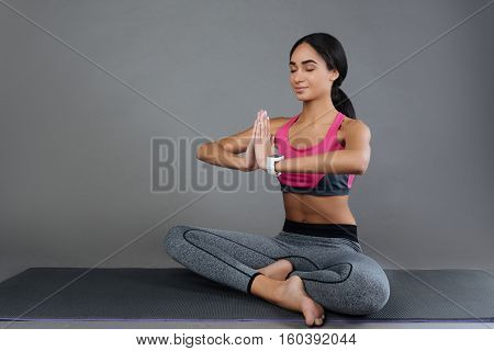 Be quiet. Attractive sportswoman sitting cross-legged on the mat wearing fitness suit keeping her eyes closed while doing yoga exercises
