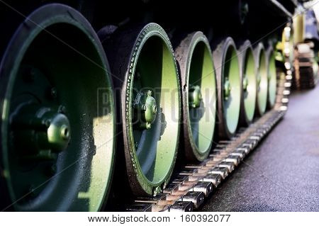 Detail shot with green tank tracks and wheels during military parade
