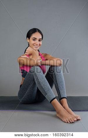 Have a pause. Healthy young woman touching her neck with right hand holding elbows on the knees smiling and looking at camera, isolated on grey background