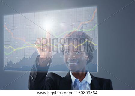 Smiling businesswoman looking at hologram financial graphs and stocks information analysing business information trends data