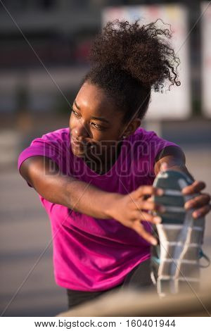 young beautiful African American woman doing warming up and stretching with her leg raised to the bridge before the morning run with the sunrise in the background