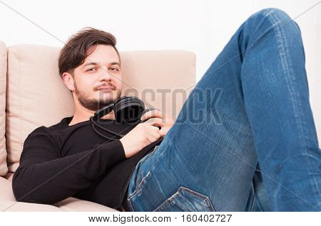 Man Laying On Sofa Holding Headphones And Relaxing