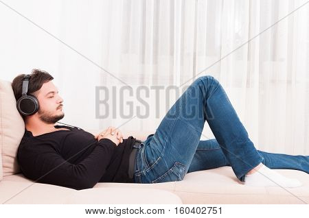 Man Laying On Sofa Wearing Headphones And Relaxing