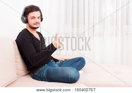 Man Sitting On Sofa Wearing Headphones Showing Thumb Up