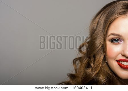 Cropped image of a beautiful, smiling woman looking at camera, half face on gray background. Place for text