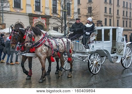 POLAND KRAKOW - JANUARY 01 2015: Horse carriages in oldtown in a first day of New Year 2015. Krakow is the second largest and one of the oldest cities in Poland.